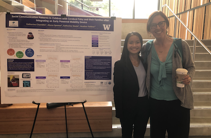 Summer research intern Katherine Chamblin and Heather Feldner standing next to a research poster presentation.