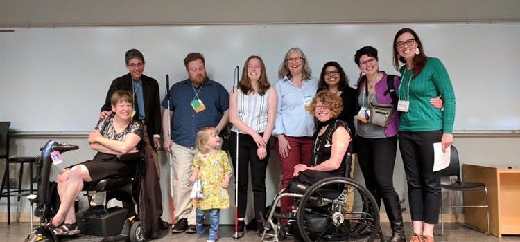 A group of people on a stage, some in scooters, some in wheelchairs, and some standing. Photo of speakers and attendees at the Pacific Western Disability Studies Conference May 2019