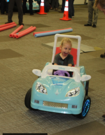 toddler driving a toy car