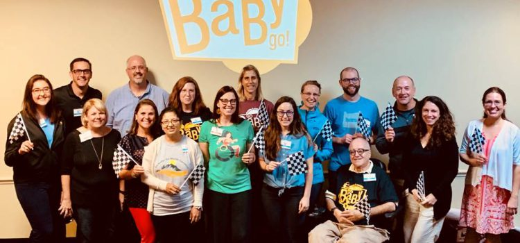 A group of diverse people standing and seated in wheelchairs at the Go Baby Go Summit, in front of a screen projected Go Baby Go logo.