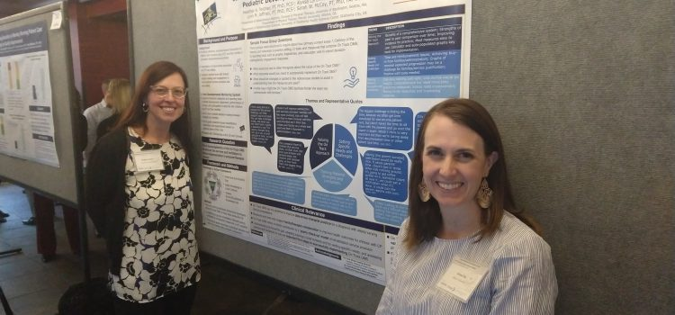 Two researchers, Heather Feldner and Alyssa LaForme Fiss, from Mercer University, stand in front of their research poster on implementation science.