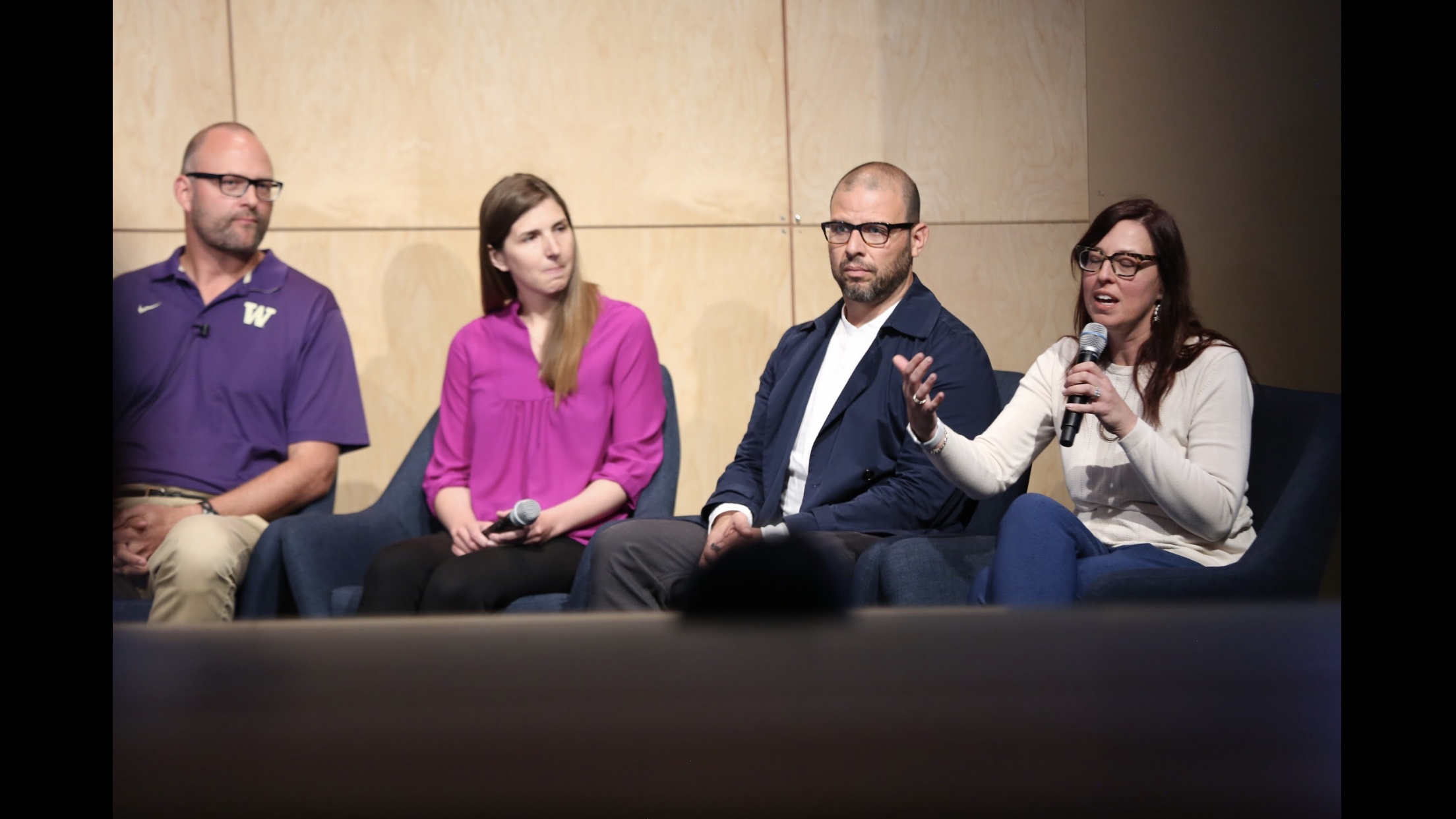 A panel of four presenters on a stage, from left to right is Jacob Wobbrock, Kat Steele, Oscar Murillo, and Heather Feldner, who is speaking into the microphone