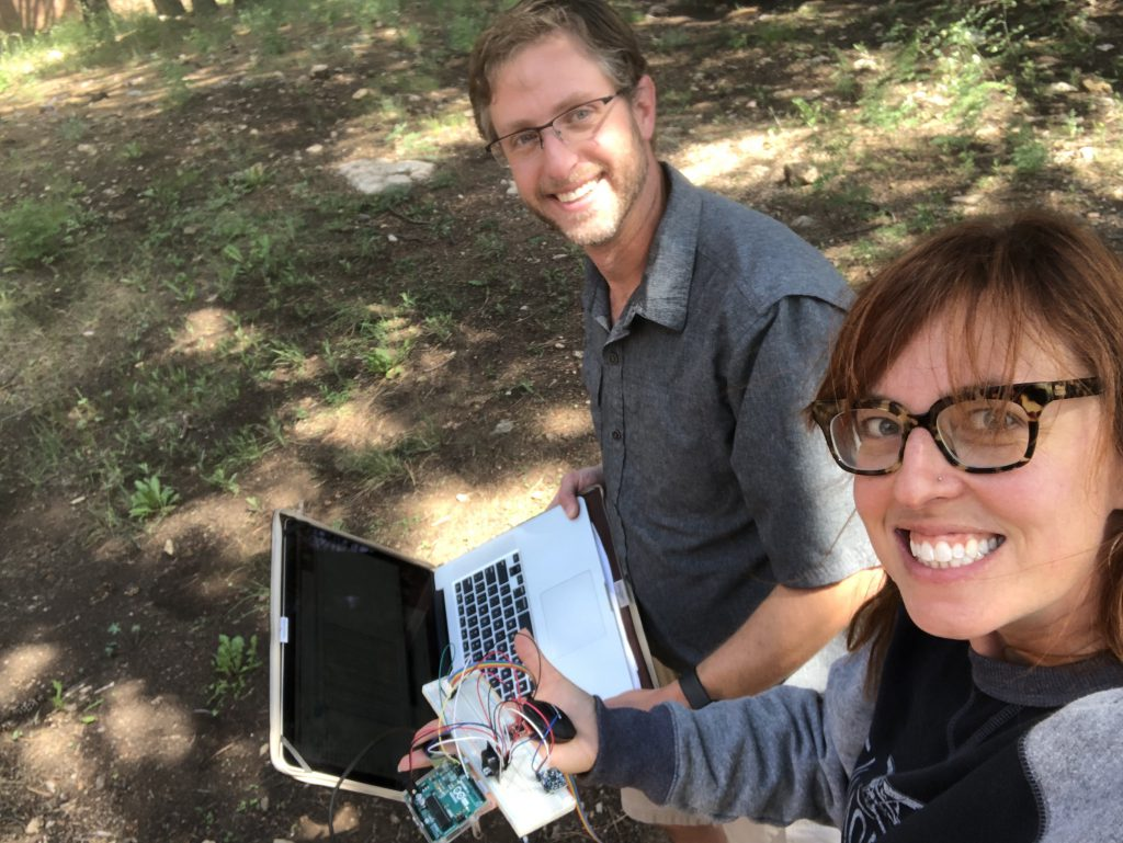 Two researchers, Kyle Winfree and Heather Feldner, are outside. Heather is smiling in the foreground and holding up a circuit board, and Kyle is smiling in the background, holding a laptop computer.