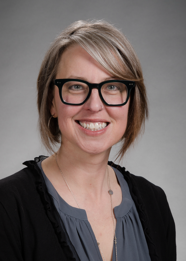 image of heather feldner, a woman with short gray hair, wearing dark rimmed glasses, a gray shirt, and black sweater, smiling at the camera